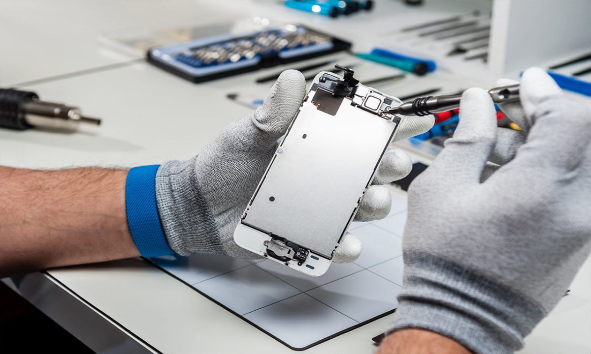 Technician wearing gloves and repairing a smartphone